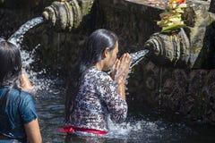 De Balinese families komen aan de heilige bronwatertempel van Tirta Empul in Bali, Indonesië hun ziel bidden en reinigen stock foto's