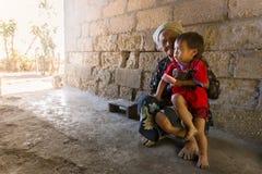 De Balinese Hindoese grootmoeder houdt op haar kleinkind onder basisschuilplaats royalty-vrije stock foto
