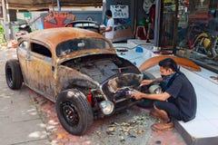 De Balinese mens vernieuwt oude auto stock foto