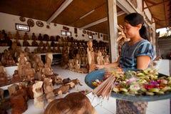 De Balinese vrouw maakt het aanbieden aan de goden Royalty-vrije Stock Afbeeldingen