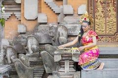 De Balinese vrouw zet dienstenaanbod in tempeldeur stock foto's