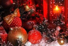 De ballen en de Kerstmisklok zijn behandeld met sneeuw in het licht van een rode lantaarn op de achtergrond van Nieuwjaar` s land Royalty-vrije Stock Afbeeldingen