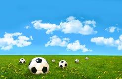 De ballen van het voetbal op een gebied van gras Stock Foto