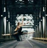 De ballerina die in streng springen stelt op de weg en de sporen royalty-vrije stock fotografie