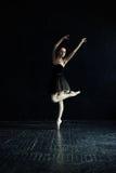 De ballerina in een zwarte kleding in een lege donkere zaal Royalty-vrije Stock Foto