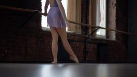 De ballerina maakt oefeningen voor voet opleiding stock videobeelden