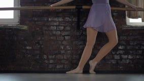De ballerina maakt oefeningen voor voet opleiding stock video
