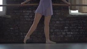 De ballerina maakt oefeningen voor voet opleiding stock footage