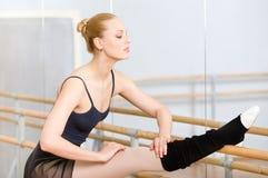 De ballerina rekt zich dichtbij staaf uit Stock Foto's