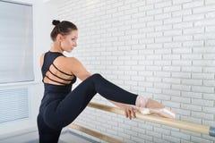 De ballerina rekt zich dichtbij staaf uit bij balletstudio, drie kwart lengteportret royalty-vrije stock foto