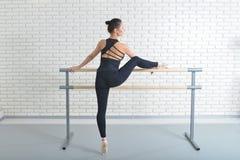 De ballerina rekt zich dichtbij staaf uit bij balletstudio, volledig lengteportret stock afbeelding
