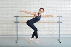 De ballerina rekt zich dichtbij staaf uit bij balletstudio, volledig lengteportret Royalty-vrije Stock Foto