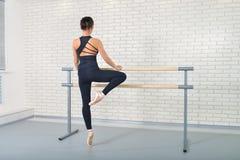 De ballerina rekt zich erachter dichtbij staaf uit bij balletstudio, volledig lengteportret, spruit van royalty-vrije stock fotografie