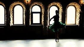 De ballerina spint op haar tenen in een groene kleding stock videobeelden