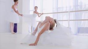 De ballerina van het kindmeisje in witte tutu doet rekoefeningen op balletles stock footage