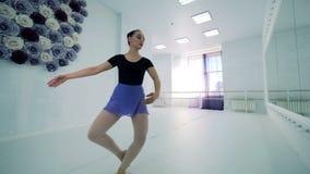 De ballerina voert het dansen bewegingen in een studio uit stock footage