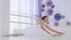 De ballerina in witte tutu en pointes rekt het zitten op streng in balletklasse uit stock video