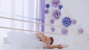 De ballerina in witte tutu rekt benen uit zittend op de vloer in balletklasse stock footage
