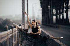 De ballerinazitting in streng stelt op de brug tegen de achtergrond van weg royalty-vrije stock afbeeldingen