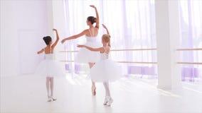De balletleraar met kinderen in tutu's danst op tiptoe in pointes in klasse stock videobeelden