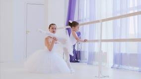 De balletleraar onderwijst meisje om benen dichtbij de staaftribune uit te rekken stock video