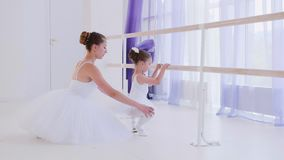 De balletleraar in witte tutu leidt meisje dichtbij de staaftribune op stock footage