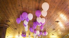 De ballons tegen wodden plafond De ballen worden gevuld met helium Stock Afbeeldingen