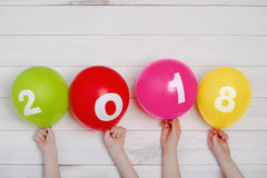 De ballons van de de holdingsregenboog van de kindhand met 2018 Stock Foto's