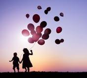 De Ballons van de kinderen in openlucht Holding samen Stock Fotografie