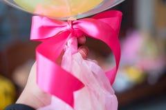 De ballons van de mensenholding, roze lint dichte omhooggaand Stock Afbeeldingen