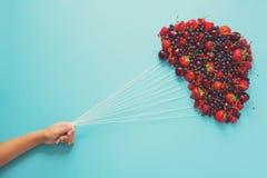 De ballons van de handholding van bessen op blauwe document achtergrond worden gemaakt die Gezond het Eten Concept Vlak leg Stock Foto