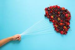 De ballons van de handholding van bessen op blauwe document achtergrond worden gemaakt die Gezond het Eten Concept Vlak leg Royalty-vrije Stock Foto's