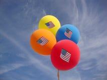 De Ballons van de onafhankelijkheidsdag tegen blauwe hemel met de vlaggen van de V.S. royalty-vrije stock fotografie