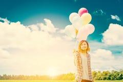De ballons van de vrouwenholding op weide en blauwe hemel met zonsopgang Royalty-vrije Stock Afbeeldingen