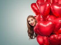 De ballonsharten van de meisjesholding Verraste Vrouw op Witte Achtergrond Verrassing, valentijnskaartenmensen en de dagconcept v royalty-vrije stock fotografie