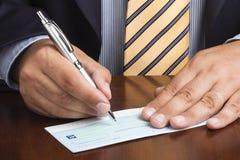 De Ballpointband van zakenmanwriting blank check Stock Afbeeldingen