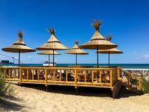 De bambú, de lámina, parasoles de playa de la paja en la playa en la ciudad de Anapa fotografía de archivo libre de regalías