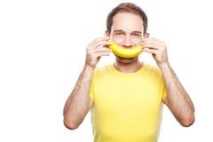 De banaan van de jongensholding zoals zijn glimlach Stock Foto