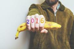 De banaan van de mensenholding in zijn hand, cijfers op vingers Stock Foto's