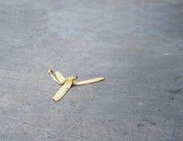 De banaanschil werd verlaten op de concrete vloer Het gevaar kan uitglijden royalty-vrije stock afbeelding