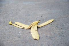 De banaanschil werd verlaten op de concrete vloer Het gevaar kan uitglijden royalty-vrije stock afbeeldingen