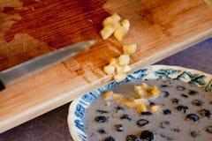De Bananen van de besnoeiing die in een Kom Graangewas worden geschaafd Stock Fotografie