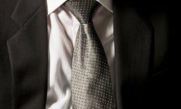 De band van de werkgever De zakenman draagt zijn donker grijs jasje op het witte overhemd met een elegante grijze band stock afbeelding