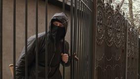 De bandietenmens in zwarte masker en kap met honkbalknuppel kruipt door omheiningsnetwerk stock footage