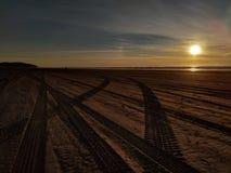 De bandsporen van het zonsondergangstrand stock afbeeldingen