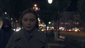 De bang gemaakte dame wordt gevolgd is dief in kap op donkere stadsstraat, stedelijke misdaad stock footage