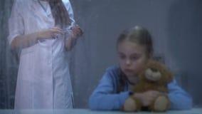 De bang gemaakte teddybeer van de meisjesholding, verpleegster met spuit op achtergrond, regenachtige dag stock videobeelden