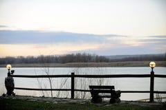 De bank en de lantaarns zijn een mooie plaats voor eenzaamheid over de rivier Royalty-vrije Stock Foto