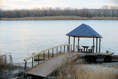 De bank en de lantaarns zijn een mooie plaats voor eenzaamheid over de rivier Stock Foto