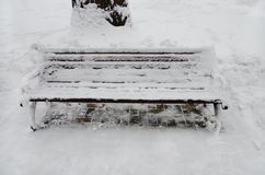 De bank in het park is behandeld met sneeuw stock foto's